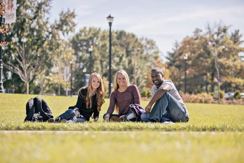 Three students sitting on the grass smiling at the camera