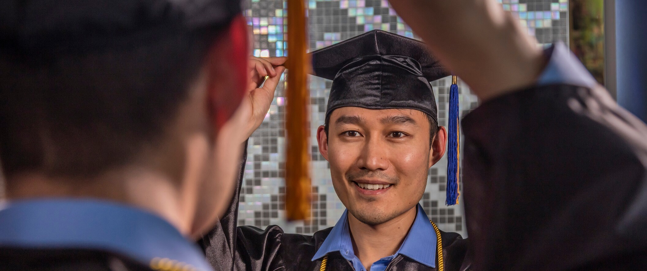 guy in graduation cap and gown looking in mirror