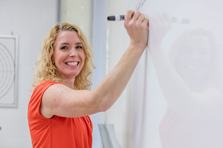 Woman drawing on a whiteboard and smiling