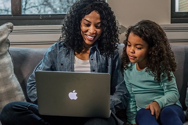 mom with daughter working on laptop from a couch