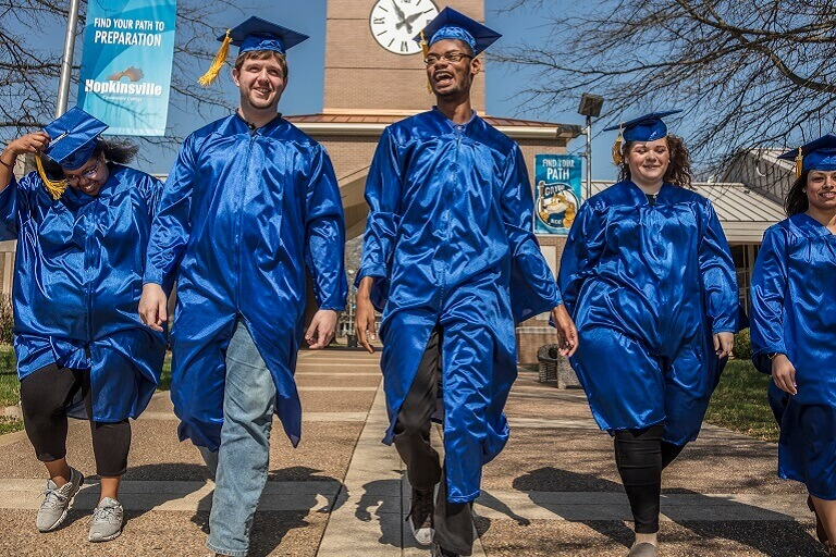graduates walking in caps and gowns on campus