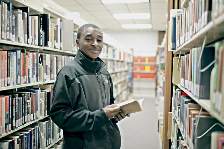 african american male reading book in library